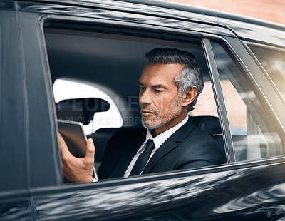 Buy stock photo Cropped shot of a handsome mature businessman using a tablet while sitting in the backseat of a car during his morning commute