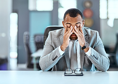 Buy stock photo Shot of a young businessman looking stressed out in an office