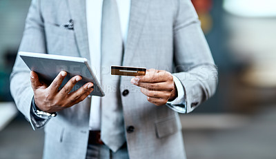Buy stock photo Closeup shot of an unrecognizable businessman using a credit card and a digital tablet in an office