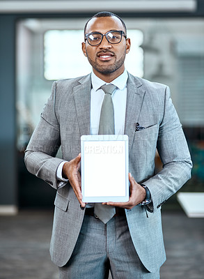 Buy stock photo Portrait of a young businessman holding up a digital tablet with a blank screen in an office