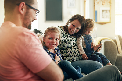 Buy stock photo Shot of young man and woman using a digital digital with their daughter's at home