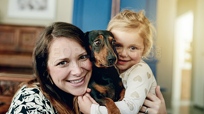 Buy stock photo Portrait of a mother and her little daughter bonding with their dog at home