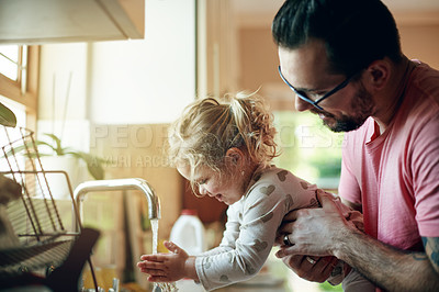 Buy stock photo Shot of a father helping his little daughter wash her hands at home
