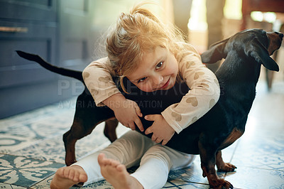 Buy stock photo Portrait of an adorable little girl playing with her pet dog at home