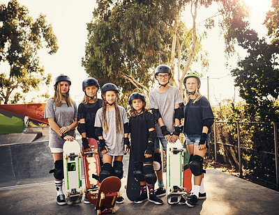 Buy stock photo Portrait of a group of young girls skateboarding together at a skatepark