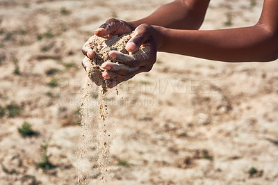 Buy stock photo Shot of an unrecognizable person holding two hands full of sand showing how dry the area is outside