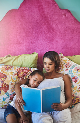 Buy stock photo Shot of a mother reading a story to her little daughter at home