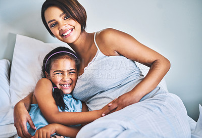 Buy stock photo Portrait of a cheerful little girl relaxing on the bed with her pregnant mother at home during the day