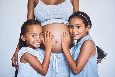 Buy stock photo Portrait of two cheerful little girls  standing next to their pregnant mother at home during the day