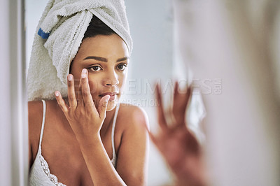 Buy stock photo Shot of an attractive young woman looking at her face in the bathroom mirror