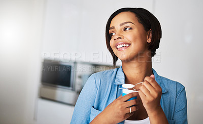 Buy stock photo Shot of an attractive young woman eating a tub of yoghurt at home