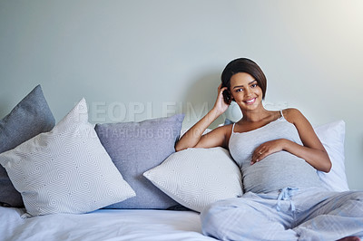 Buy stock photo Shot of a pregnant young woman relaxing on the bed at home