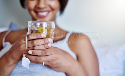 Buy stock photo Cropped shot of a young woman relaxing at home with a glass of tea