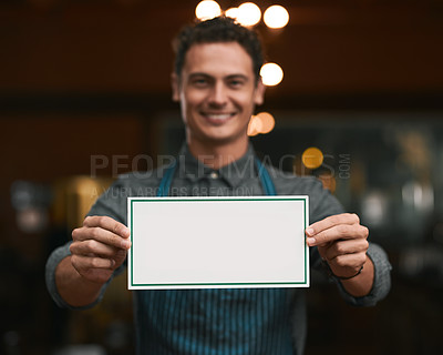Buy stock photo Portrait of a cheerful young man holding a sign while standing inside of a beer brewery during the day