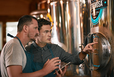 Buy stock photo Shot of two young working men doing inspection of their beer making machinery inside of a beer brewery during the day