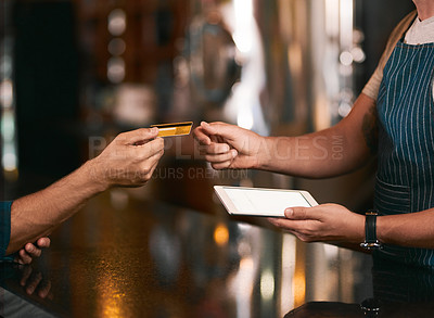 Buy stock photo Shot of two unrecognizable people making an exchange in payment with a credit card inside of a beer brewery during the day