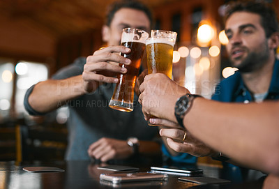 Buy stock photo Shot of three cheerful young men having a celebratory toast with beer while sitting at a table inside of a beer brewery during the day