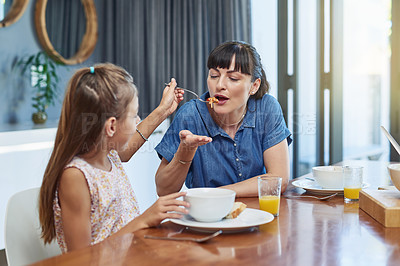 Buy stock photo Shot of a mother enjoying a meal with her little daughter at home