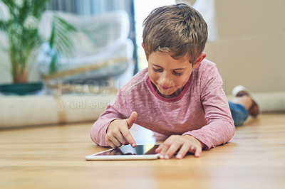 Buy stock photo Shot of an adorable little boy using a digital tablet at home on moving day
