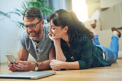 Buy stock photo Shot of a husband and wife using a mobile phone together on moving day