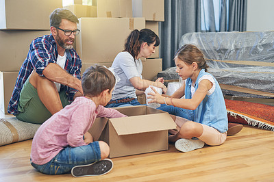 Buy stock photo Shot of a family of four helping each other pack boxes on moving day