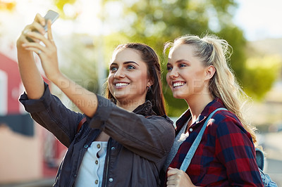 Buy stock photo Cropped shot of two beautiful female friends taking a selfie in the city