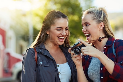 Buy stock photo Cropped shot of two beautiful female friends looking at photographs on a camera in the city