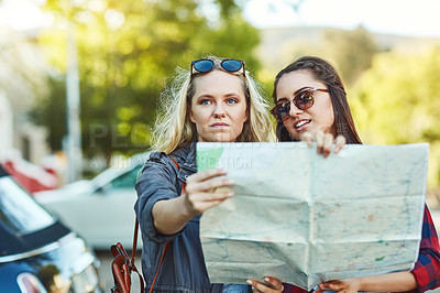 Buy stock photo Cropped shot of two beautiful female friends looking at a map for directions in the city