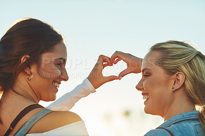 Buy stock photo Rearview shot of two beautiful female friends making a heat shape with their hands in nature