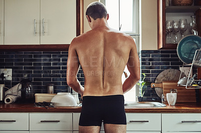 Buy stock photo Rearview shot of a muscular young man standing in his underwear while preparing food in the kitchen at home