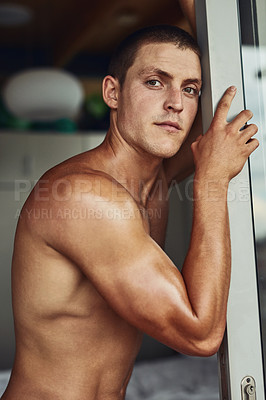 Buy stock photo Portrait of a confident young shirtless man leaning against a doorway in the kitchen at home