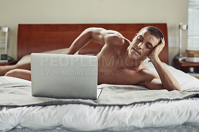 Buy stock photo Shot of a carefree young naked man lying on his bed while being busy with his laptop at home during the day