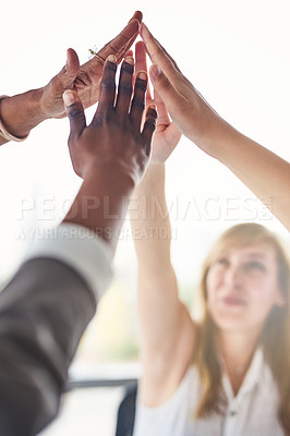 Buy stock photo Cropped shot of a group of unrecognizable businesswomen giving each other a high five in the office
