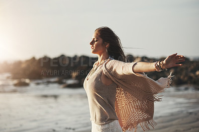 Buy stock photo Shot of an attractive young woman standing with her arms outstretched at the beach