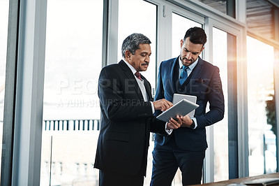 Buy stock photo Cropped shot of colleagues using a tablet in a modern office