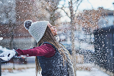 Buy stock photo Shot of a happy young woman throwing snow on a wintery day outdoors