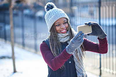 Buy stock photo Shot of a beautiful young woman taking a selfie on a snowy day outdoors
