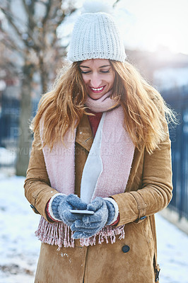 Buy stock photo Shot of an attractive young woman using a cellphone in the snow outside