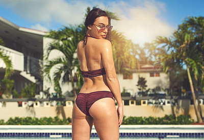 Buy stock photo Rearview shot of a beautiful young woman at the swimming pool outside