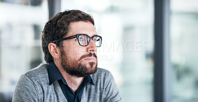 Buy stock photo Shot of a handsome young businessman looking thoughtful in an office