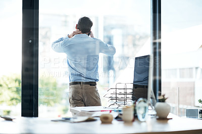 Buy stock photo Rearview shot of a young businessman talking on a cellphone in an office