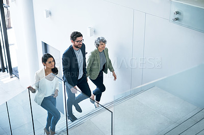 Buy stock photo Shot of a group of businesspeople walking up a staircase in an office