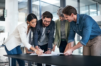 Buy stock photo Shot of a group of businesspeople going through some paperwork in an office
