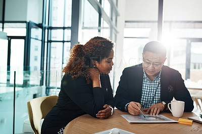 Buy stock photo Shot of two businesspeople going through some paperwork in an office