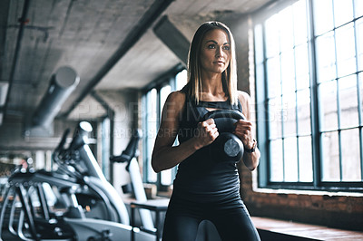 Buy stock photo Shot of a young woman working out with a kettle bell in a gym