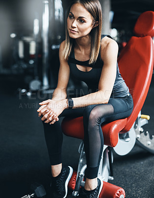 Buy stock photo Shot of an attractive young woman looking thoughtful during a workout in the gym