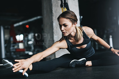 Buy stock photo Shot of an attractive young woman stretching during her workout in a gym