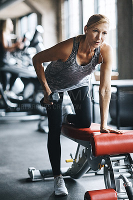 Buy stock photo Shot of a mature woman lifting weights at the gym