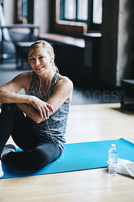 Buy stock photo Cropped shot of an attractive young woman listening to music while working out in the gym