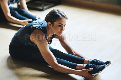 Buy stock photo High angle shot of an attractive young woman stretching before her workout in the gym
